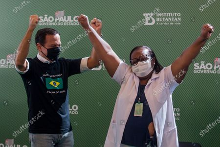 Nurse Monica Calazans, 54, and the Governor of Sao Paulo Joao Doria celebrate after she got her shot of the COVID-19 vaccine produced by China's Sinovac Biotech Ltd, at the Hospital das Clinicas in Sao Paulo, Brazil