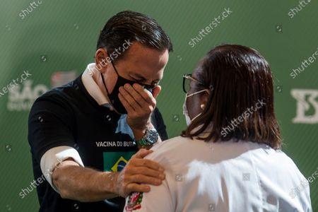 Sao Paulo Governor Joao Doria cries as he greets nurse Nurse Monica Calazans, 54, after she got her shot of the COVID-19 vaccine produced by China's Sinovac Biotech Ltd, at the Hospital das Clinicas in Sao Paulo, Brazil