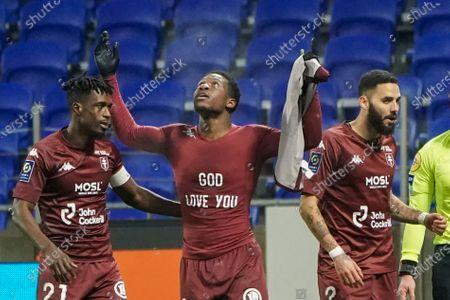 Metz's Aaron Leya Iseka, center, celebrates with his teammates John Boye, left, and Dylan Bronn after he scored his side's first goal during the French League One soccer match between Lyon and Metz, in Decines, near Lyon, central France