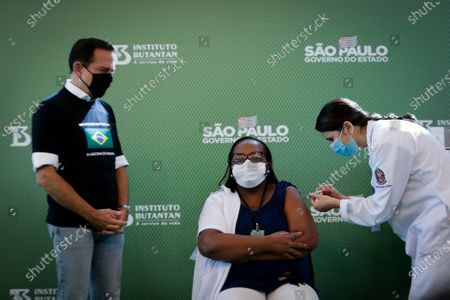Monica Calazans (C), a nurse at Hospital las Clinicas in the capital of Sao Paulo, receives the vaccine against covid-19 in the presence of the governor of the state of Sao Paulo, Joao Doria (L), in Sao Paulo, Brazil, 17 January 2021. Brazil, one of the countries in the world most affected by the coronavirus pandemic, applied the first dose of the covid-19 vaccine to the 54-year-old nurse this Sunday in Sao Paulo, at a time when the Latin American giant faces a second wave of the disease. The first dose of the vaccine developed by the Chinese laboratory Sinovac and the Brazilian Butantan Institute was administered just minutes after the approval of its emergency use by the National Health Surveillance Agency (Anvisa).