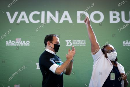 Monica Calazans (R), a nurse at the Hospital las Clinicas in the capital of Sao Paulo, raises her arm in joy after receiving the vaccine against covid-19 and while being applauded by the governor of Sao Paulo, Joao Doria (L), in Sao Paulo, Brazil, 17 January 2021. Brazil, one of the countries in the world most affected by the coronavirus pandemic, applied the first dose of the covid-19 vaccine to the 54-year-old nurse this Sunday in Sao Paulo, at a time when the Latin American giant faces a second wave of the disease. The first dose of the vaccine developed by the Chinese laboratory Sinovac and the Brazilian Butantan Institute was administered just minutes after the approval of its emergency use by the National Health Surveillance Agency (Anvisa).