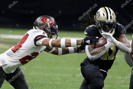 New Orleans Saints running back Alvin Kamara, right, runs against Tampa Bay Buccaneers cornerback Carlton Davis during the first half of an NFL divisional round playoff football game, in New Orleans
