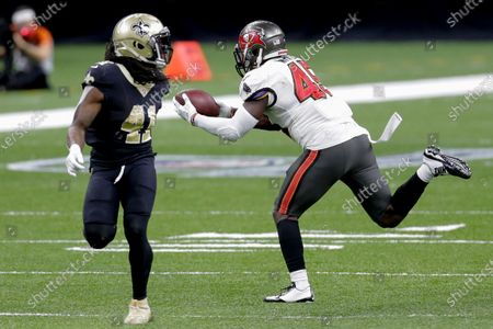 Tampa Bay Buccaneers inside linebacker Devin White, right, intercepts a pass in front of New Orleans Saints running back Alvin Kamara (41) during the second half of an NFL divisional round playoff football game, in New Orleans