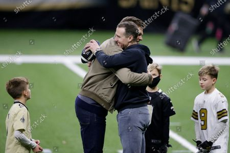 New Orleans Saints quarterback Drew Brees right, embraces Tampa Bay Buccaneers quarterback Tom Brady as Bree's children look on after an NFL divisional round playoff football game between the New Orleans Saints and the Tampa Bay Buccaneers, in New Orleans. The Tampa Bay Buccaneers won 30-20