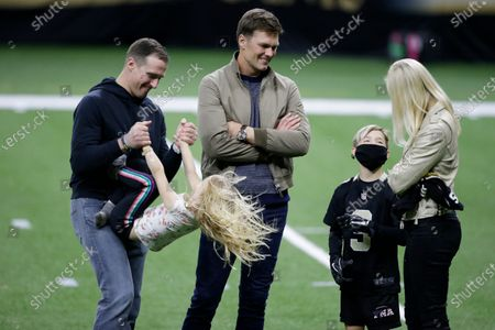 New Orleans Saints quarterback Drew Brees, left, plays with his children as Tampa Bay Buccaneers quarterback Tom Brady speaks with Brittany Brees after an NFL divisional round playoff football game between the New Orleans Saints and the Tampa Bay Buccaneers, in New Orleans. The Tampa Bay Buccaneers won 30-20