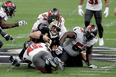 New Orleans Saints quarterback Drew Brees, center, is tackled between Tampa Bay Buccaneers' Devin White (45), Lavonte David (54) and Rakeem Nunez-Roches (56) during the first half of an NFL divisional round playoff football game, in New Orleans