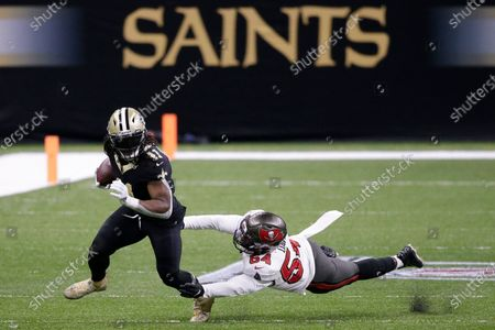 New Orleans Saints running back Alvin Kamara (41) runs past Tampa Bay Buccaneers inside linebacker Lavonte David (54) during the first half of an NFL divisional round playoff football game, in New Orleans