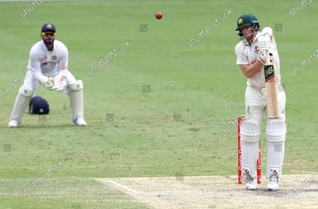Australia's Steve Smith reacts as he hits the ball to be out caught during play on day four of the fourth cricket test between India and Australia at the Gabba, Brisbane, Australia