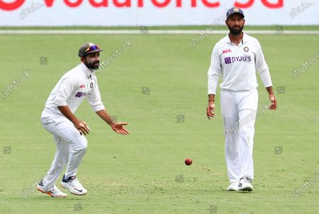 India's Ajinkya Rahane, left, reacts after taking a catch to dismiss Australia's Steve Smith as teammate India's Cheteshwar Pujara, right, watches during play on day four of the fourth cricket test between India and Australia at the Gabba, Brisbane, Australia