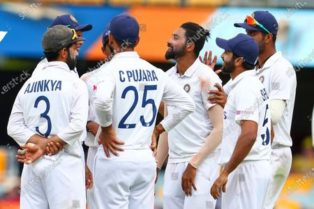 India's Mohammed Siraj, centre, is congratulated by teammates after dismissing Australia's Mitchell Starc during play on day four of the fourth cricket test between India and Australia at the Gabba, Brisbane, Australia