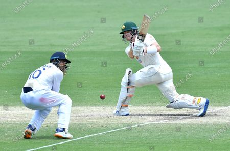 Steve Smith (R) of Australia gets runs past Mayank Agarwal (L) of India during day four of the fourth Test Match between Australia and India at the Gabba in Brisbane, Australia, 18 January 2021.