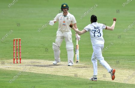 Steve Smith (L) of Australia reacts after losing his wicket to Mohammed Siraj (R) of India during day four of the fourth Test Match between Australia and India at the Gabba in Brisbane, Australia, 18 January 2021.
