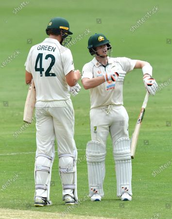 Steve Smith (R) of Australia reacts as he waits for a DRS decision after losing his wicket to Mohammed Siraj of India during day four of the fourth Test Match between Australia and India at the Gabba in Brisbane, Australia, 18 January 2021.