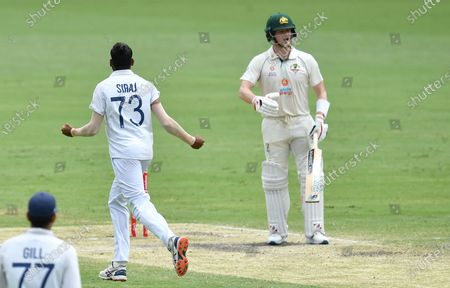 Steve Smith (R) of Australia reacts after losing his wicket to Mohammed Siraj (L, top) of India during day four of the fourth Test Match between Australia and India at the Gabba in Brisbane, Australia, 18 January 2021.