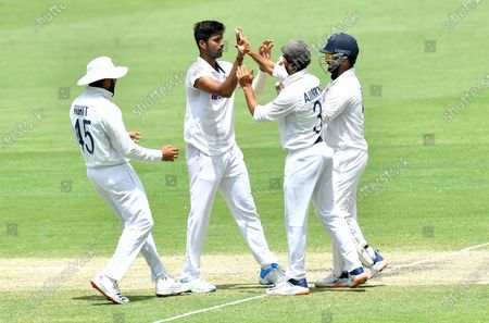Washington Sundar (2-L) of India celebrates with team mates after getting the wicket of David Warner of Australia during day four of the fourth Test Match between Australia and India at the Gabba in Brisbane, Australia, 18 January 2021.