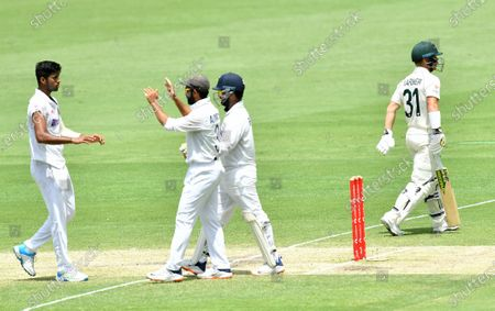 Washington Sundar (L)  of India celebrates with team mates after getting the wicket of David Warner (R) of Australia during day four of the fourth Test Match between Australia and India at the Gabba in Brisbane, Australia, 18 January 2021.
