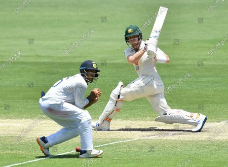 Steve Smith (R) of Australia is seen hitting the ball into Mayank Agarwal of India (L) during day four of the fourth Test Match between Australia and India at the Gabba in Brisbane, Australia, 18 January 2021.