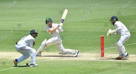 Steve Smith (C) of Australia is seen hitting the ball into Mayank Agarwal of India (L) during day four of the fourth Test Match between Australia and India at the Gabba in Brisbane, Australia, 18 January 2021.