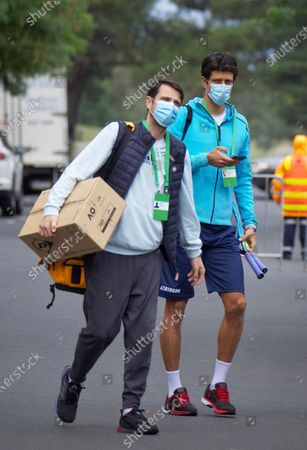 Brazilian Tennis player Marcelo Melo (R) is escorted from his hotel room to practice in Melbourne, Australia, 18 January 2021. Players who were aboard two flights that had four positive COVID-19 cases are in hard quarantine, unable to join their colleague who can train for up to five hours a day.