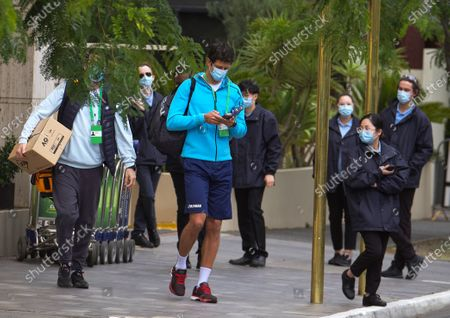 Brazilian Tennis player Marcelo Melo (C) is escorted from his hotel room to practice in Melbourne, Australia, 18 January 2021. Players who were aboard two flights that had four positive COVID-19 cases are in hard quarantine, unable to join their colleague who can train for up to five hours a day.