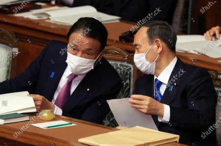 Japanese Prime Minister Yoshihide Suga (R) chats with Finance Minister Taro Aso (L) after he delivered a policy speech at Lower House's plenary session at the National Diet in Tokyo on Monday, January 18, 2021. Diet convenes 150-day regular session on January 18 amid outbreak of the new coronavirus.