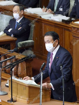 Wearing a face mask, Japan's Finance Minister Taro Aso (R) delivers a speech at a House of Representatives plenary session of the parliament as Prime Minister Yoshihide Suga (L) is seen in the background in Tokyo, Japan, 18 January 2021. Finance Minister Taro Aso said he will take measures to restore the economy hit by the Covid-19 coronavirus pandemic.