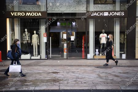 Stock Image of People wearing protective face masks walk in front of a closed Vero Moda and Jack Jones clothes shop the first day of the closure of non-essential shops during the coronavirus disease (COVID-19) outbreak, in a shopping street of Geneva, Switzerland, 18 January 2021. From 18 January 2021, Switzerland closes non-essential shops and introduces  mandatory teleworking as well as the extension to the end of February of restaurant and sports facilities closures in a move to drastically reduce coronavirus infections.