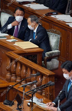 Japan's Prime Minister Yoshihide Suga (C) talks with Deputy Prime Minister and Finance Minister Taro Aso during the Lower House's plenary session of the 204th Ordinary Diet session