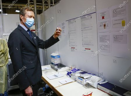 Grand Duke Henri of Luxembourg shows a BioNTech/Pfizer vaccine during a visit to the vaccination center at Hall Victor Hugo, in Luxembourg, 18 January 2021. Luxembourg citizens as well as cross-border workers receive an appointment for vaccination against COVID-19 thanks to the code provided in the invitation received by post. In the vaccination strategy, the first people to be vaccinated were health professionals and hospital staff.