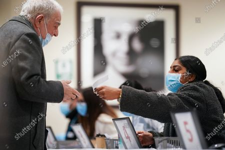 Stock Image of At Lord's Cricket Ground, below a portrait of cricketer David Gower, volunteers register local residents for the Pfizer Covid 19 vaccine at The Thomas Lord Suite, upstairs from the Lords' Tavern pub