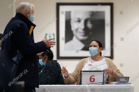 At Lord's Cricket ground, below a portrait of cricketer David Gower, patients register for the Pfizer Covid 19 vaccine at The Thomas Lord Suite, upstairs from the Lords' Tavern pub
