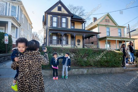 Stock Picture of Alexis Upshaw, left, holding 2-year-old Ari Upshaw, takes a photo as Ty Upshaw, 7, right, adjusts the mask of his sister, Mila Upshaw, 5, in front of the birthplace of Dr. Martin Luther King, Jr., the Martin Luther King Jr. holiday, in Atlanta
