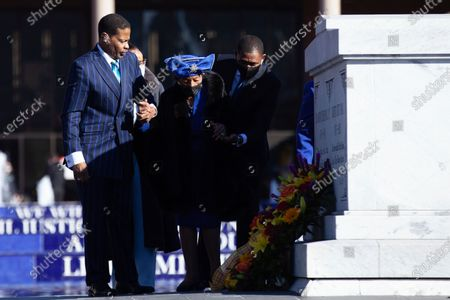 Christine King Farris, sister of Martin Luther King, Jr., center, is helped by her son Isaac Newton Farris, Jr., left, and an unidentified man after laying a wreath at the crypt, in honor of Martin Luther King Jr. Day, in Atlanta