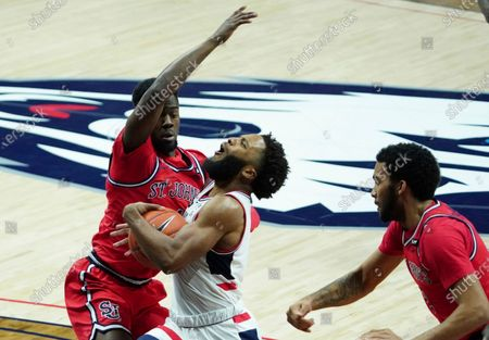 UConn guard R.J. Cole, center, drives against St. John's Greg Williams Jr., left, during the first half of an NCAA college basketball game in Storrs, Connecticut