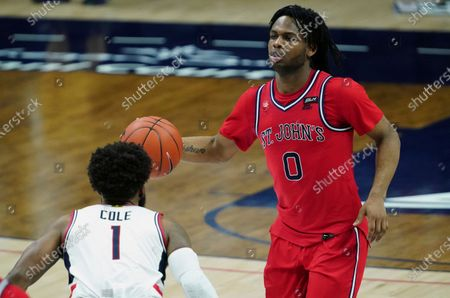 Stock Picture of St. John's guard Posh Alexander (0) returns the ball against Connecticut guard R.J. Cole (1) in the second half of an NCAA college basketball game in Storrs, Conn