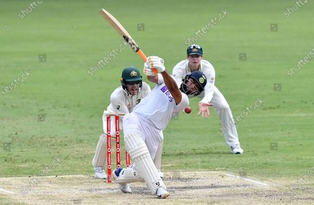 Rishabh Pant (centre) of India gets four byes past Tim Paine (left) and Steve Smith (right) of Australia during day five of the fourth Test Match between Australia and India at the Gabba in Brisbane, Australia, 19 January 2021.