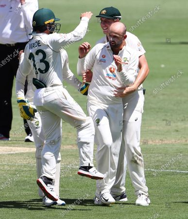 Australia's Nathan Lyon is congratulated by teammates Matthew Wade, left, and Cameron Green after taking the wicket of India's Shubman Gill during play on the final day of the fourth cricket test between India and Australia at the Gabba, Brisbane, Australia