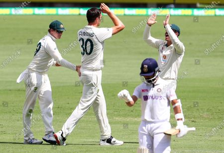 Australia's Pat Cummins is congratulated by teammates Steve Smith, left, and David Warner, right, after dismissing India's Ajinkya Rahane during play on the final day of the fourth cricket test between India and Australia at the Gabba, Brisbane, Australia