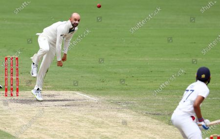 Australia's Nathan Lyon, left, bowls to India's Shubman Gill during play on the final day of the fourth cricket test between India and Australia at the Gabba, Brisbane, Australia