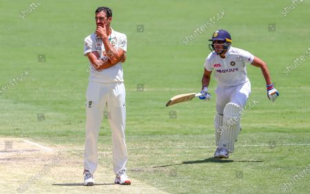 Australia's Mitchell Starc, left, reacts as India's Shubman Gill runs during play on the final day of the fourth cricket test between India and Australia at the Gabba, Brisbane, Australia