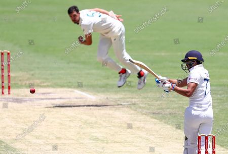 India's Shubman Gill, right, hits a delivery from Australia's Mitchell Starc during play on the final day of the fourth cricket test between India and Australia at the Gabba, Brisbane, Australia