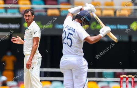 Australia's Mitchell Starc, left, reacts after bowling to India's Cheteshwar Pujara during play on the final day of the fourth cricket test between India and Australia at the Gabba, Brisbane, Australia