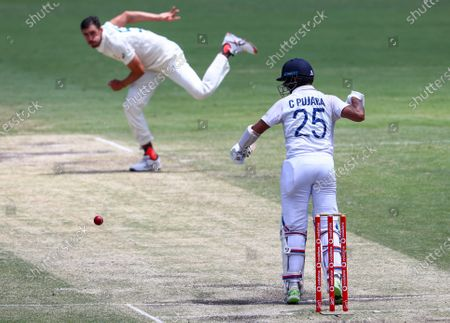 India's Cheteshwar Pujara plays at a ball from Australia's Mitchell Starc during play on the final day of the fourth cricket test between India and Australia at the Gabba, Brisbane, Australia