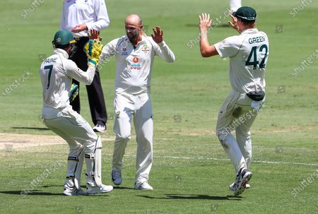 Australia's Nathan Lyon, centre, is congratulated by teammates Tim Paine, left, and Cameron Green after taking the wicket of India's Shubman Gill for 91 runs during play on the final day of the fourth cricket test between India and Australia at the Gabba, Brisbane, Australia