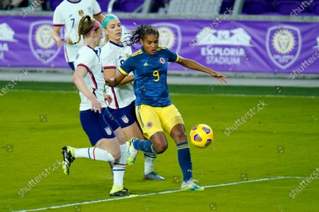 Colombia forward Kena Romero (9) moves the ball past United States defender Becky Sauerbrunn, left, and midfielder Julie Ertz, center, during the first half of an international friendly soccer match, in Orlando, Fla