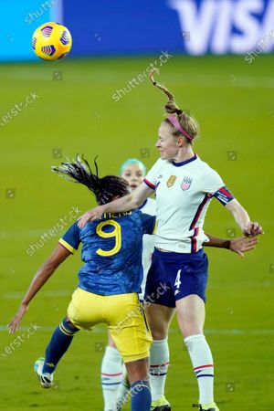 United States defender Becky Sauerbrunn (4) heads the ball away from Colombia forward Kena Romero (9) during the first half of an international friendly soccer match, in Orlando, Fla