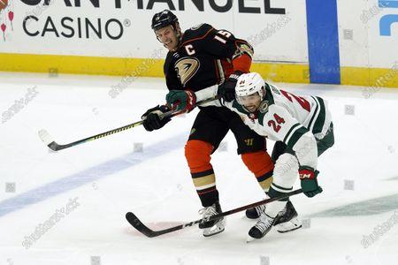 Anaheim Ducks' Ryan Getzlaf (15) is defended by Minnesota Wild defenseman Matt Dumba (24) during the third period of an NHL hockey game, in Anaheim, Calif