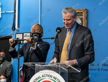 New York City mayor Bill de Blasio speaks as Reverend Al Sharpton adjusts microphone during Martin Luther King celebration at NAN headquarters