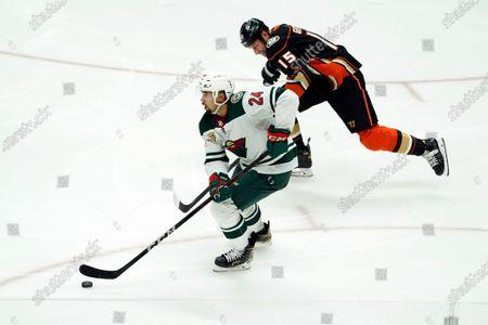 Minnesota Wild defenseman Matt Dumba (24) skates past Anaheim Ducks center Ryan Getzlaf (15) during the third period of an NHL hockey game, in Anaheim, Calif