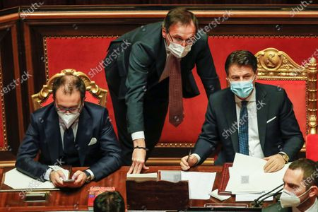 From left, Justice Minister Alfonso Bonafede, Minister for Regional Affairs Francesco Boccia and Premier Giuseppe Conte attend a debate at the Senate prior to a confidence vote, in Rome, . Conte fights for his political life with an address aimed at shoring up support for his government, which has come under fire from former Premier Matteo Renzi's tiny but key Italia Viva (Italy Alive) party over plans to relaunch the pandemic-ravaged economy